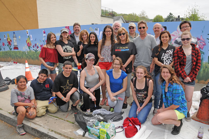 Students, teachers and officials pose in front of new mural on Beekman Avenue that they painted. Photo: Sunny McLean