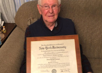 Alfred Abraham poses with his diploma from New York University